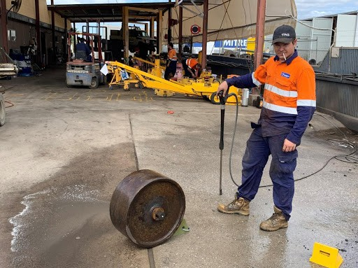 one of our staffs holding a pressure hose to clean the metal wheel